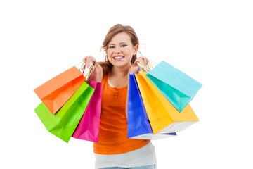 junge lachende frau mit bunten einkaufstaschen