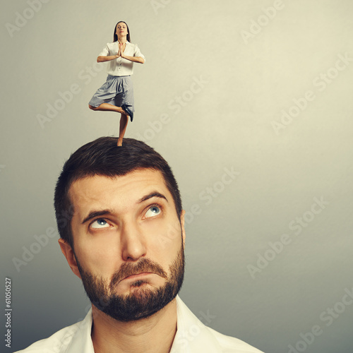 woman standing on the head of thoughtful man