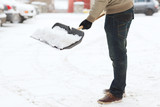 closeup of man shoveling snow from driveway