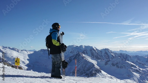 Man with snowboard standing on top of snowy mountain, Hintertux