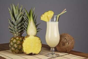 Pina Colada mit Kokosnuss und Ananas vor grauem Hintergrund