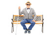 Blind senior man seated on bench isolated on white background