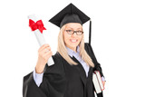 Female student in graduation gown holding boos and a diploma