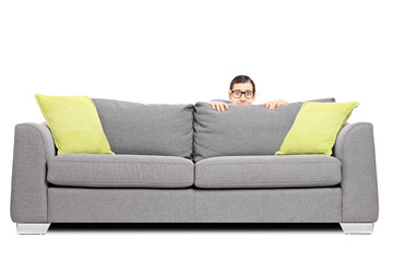 Frightened man hiding behind a sofa