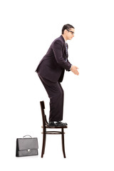 Male businessman standing up on chair ready to jump