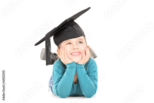 Adorable girl with graduation hat laying down and daydreaming
