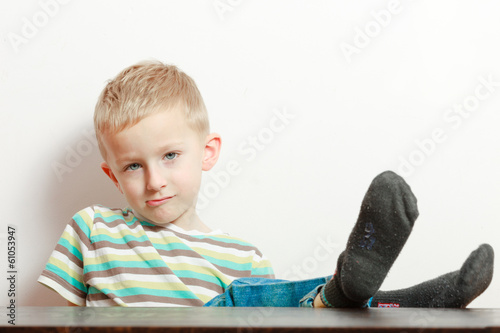 Manners. Bored boy child kid with feet on the table. At home.