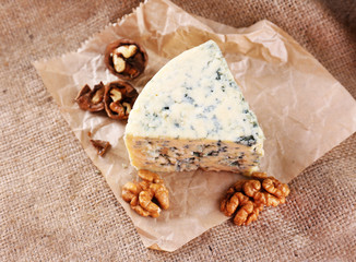 Tasty blue cheese with nuts, on burlap background