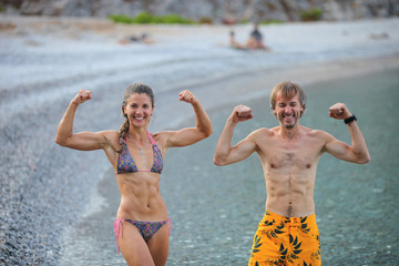 Young woman and man flexing their muscles at beach