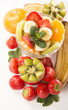 Bananas, kiwi and strawberry and glass bowl with fresh fruits