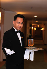 waiter or butler in uniform at five star hotel corridor