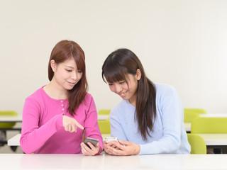 スマートフォンを持つ若い女性二人