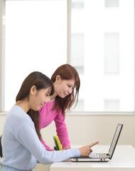 ノートパソコンを使う女性二人
