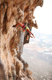 Young female rock climber resting while hanging on rope