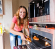 beautiful woman putting meat into oven