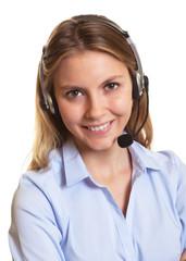 Freundliche Kundenberaterin mit Headset schaut zur Kamera