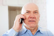 mature man speaks by phone