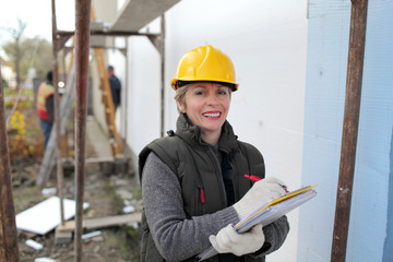 Smiling female inspector at construction site examine works