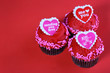 Chocolate cupcakes with red hearts, over red background
