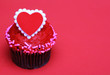 Chocolate cupcake with red heart on the top, over red background