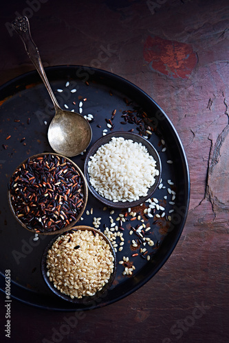 Various types of rice on old spoons and in cups