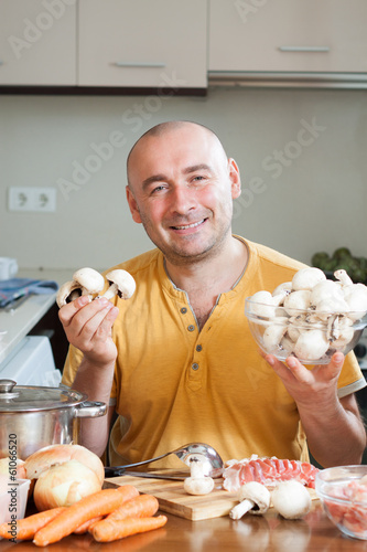 Man with mashrooms in kitchen