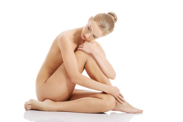 Beautiful caucasian naked woman sitting with fresh clean skin.