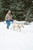 Woman with a white dog on a walk in the woods during a snowfall