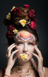 Woman in art makeup and hairstyle with flower in her mouth