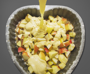 Pouring batter on apples in baking dish , isolated