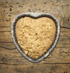 Sponge cake heart, baking dish, background of wood
