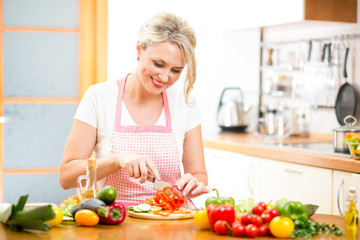 Cute woman cuts paprika for salad sitting at the kitchen table