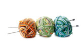 three melange ball of wool and knitting needles on white backgro