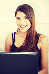 Young woman's working on laptop and smiling to camera.