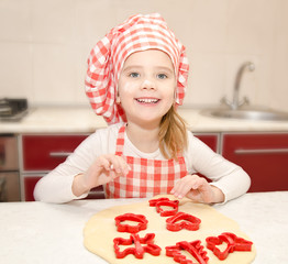 Little girl cuts dough with form for cookies