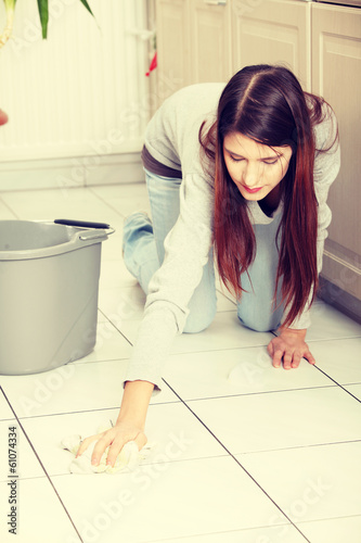 Young woman cleaning flor