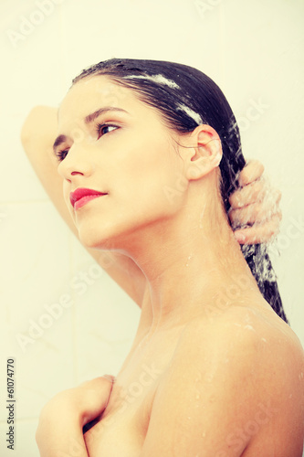 Beautiful young woman washing her hairs