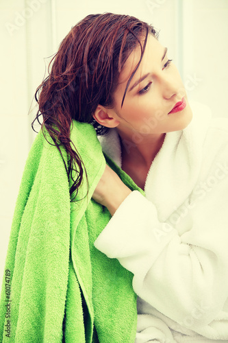 Beautiful young woman wipes her hairs