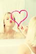 Young beautiful woman drawing big heart on mirror.