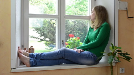 wife sit on sill and watch through window waiting for husband