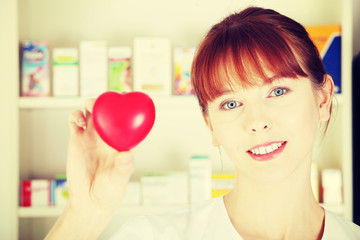 Woman in pharmacist uniform showing heart