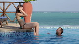 Man splashing his girlfriend sitting by the pool
