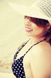 Happy pretty girl in straw hat sitting on beach.