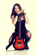 Attractive girl squats with electric guitar.