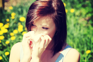 Girl with runny nose, having allergy on meadow.