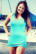 Beautiful young woman standing in yacht harbor.
