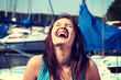 Woman in front of yacht boat is laughing with closed eyes.