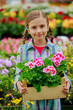 Planting, flowers - girl holding flowers in garden center