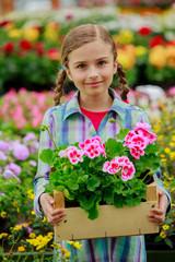 Planting, flowers - girl holding flowers in garden center