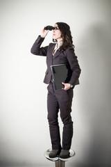 beautiful young businesswoman with binocular